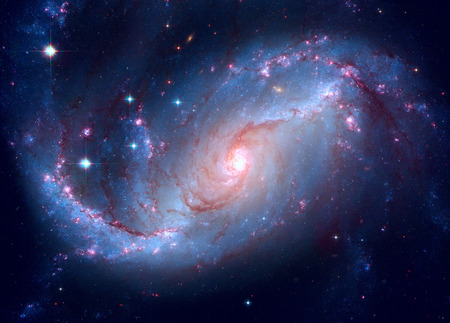 dorado: Stellar Nursery in the arms of NGC 1672. NGC 1672 is a barred spiral galaxy located in the constellation Dorado. Retouched image. Elements of this image furnished by NASA.