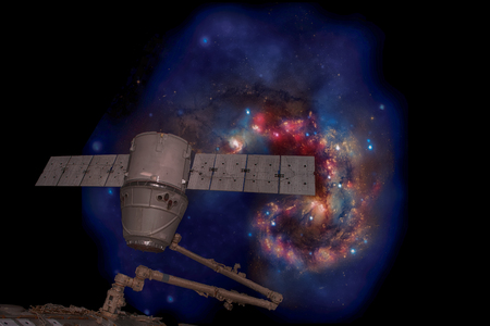 SpaceX Dragon over spiral galaxy. Elements of this image furnished by NASA.