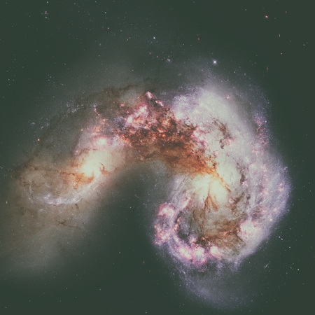 corvus: The Antennae Galaxies or NGC 4038 or NGC 4039 are undergoing a galactic collision. Located in the constellation Corvus. Retouched image. Elements of this image furnished by NASA. Stock Photo