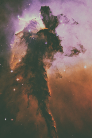 A billowing tower of gas and dust rises from the stellar nursery known as the Eagle Nebula. Space with stars, nebula and galaxy. Elements of this image furnished by NASA. Stock Photo