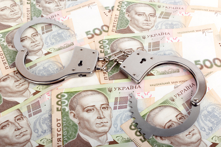 atonement: Ukrainian currency and handcuffs, the concept of crime. Stock Photo