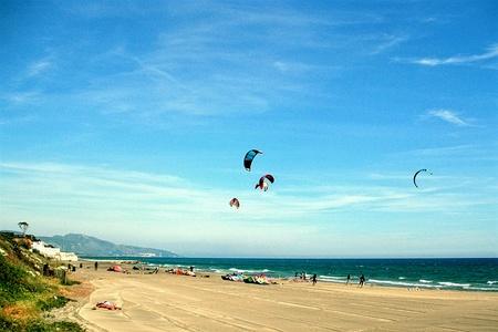 flying kites: Flying kites and sunbathing on the beach  Lago di Fondi, Italy Stock Photo