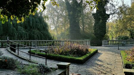 southwark: Quiet Ada Salter Garden in Southwark Park London -  path to trees and flowers in autumn sunlight Stock Photo