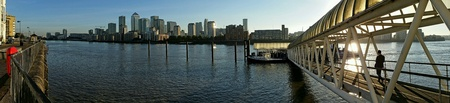 Panorama of London with worker boarding from Thames pier and city architecture
