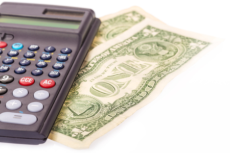monthly salary: Calculator and two, one Dollar Notes on white background