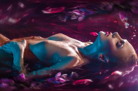 Chica caucásica húmeda desnuda posando en el oscuro estudio con agua Foto de archivo - 65289329