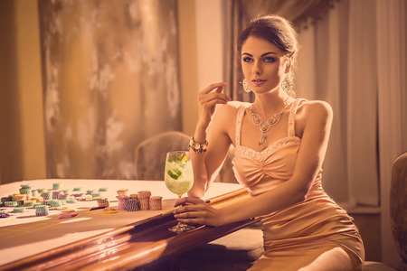 Beautiful young model drinking cocktail in casino Stok Fotoğraf