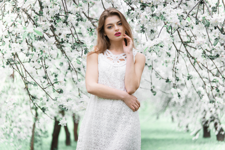 young beautiful model in white dress in the summer garden
