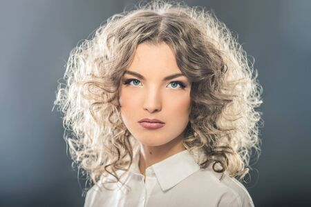 Portrait of beautiful young girl with luxuriant hair curling.