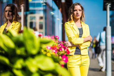 pelo castaño claro: Hermosa chica está de pie sobre las flores en la ciudad Foto de archivo