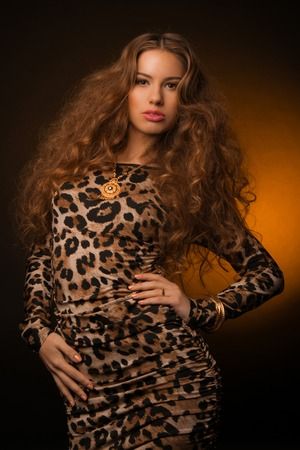Girl in leopard dress and black shoes on brown background Stock fotó