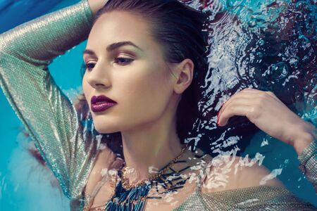 young woman beauty portrait in water with professional makeup Foto de archivo - 134397239