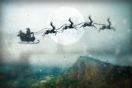 Santa flying on sky over over the mountains. Marry Christmas and happy holiday. Foto de archivo - 135092330
