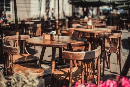 View of old cozy cafe in old city. Wooden tables and chairs in an outdoor cafe Foto de archivo - 135391750