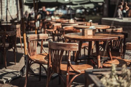 View of old cozy cafe in old city. Wooden tables and chairs in an outdoor cafe Foto de archivo - 135391753