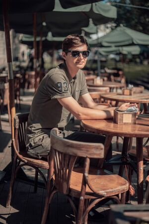 Handsome man sits in cozy cafe in old city. Wooden tables and chairs in an outdoor cafe Foto de archivo - 135382650