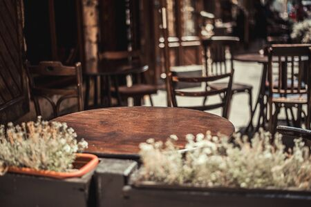 View of old cozy cafe in old city. Wooden tables and chairs in an outdoor cafe Foto de archivo - 135391758
