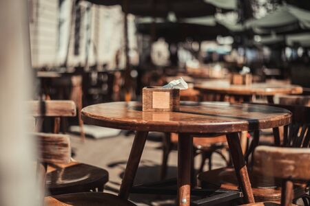 View of old cozy cafe in old city. Wooden tables and chairs in an outdoor cafe Foto de archivo - 135385958