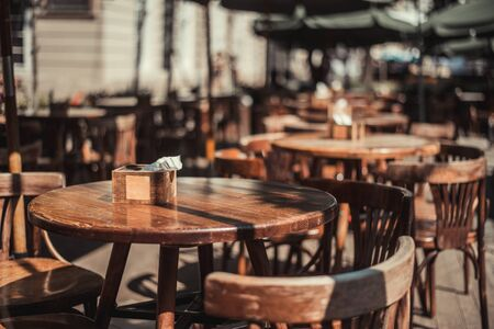View of old cozy cafe in old city. Wooden tables and chairs in an outdoor cafe Foto de archivo - 135385959