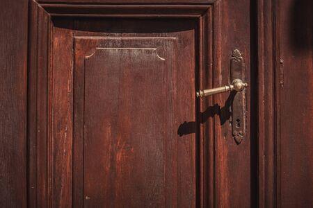 old wooden door in old city. Brown door with antique handle Foto de archivo - 135222627