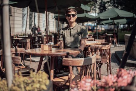 Handsome man sits in cozy cafe in old city. Wooden tables and chairs in an outdoor cafe Foto de archivo - 135382094
