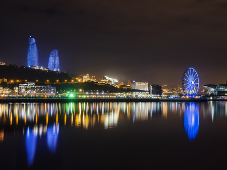 Night view of Baku with the Flame Towers skyscrapers, television tower and the seaside of the Caspian sea. 新闻类图片