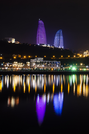 Night view of Baku with the Flame Towers skyscrapers, television tower and the seaside of the Caspian sea. Редакционное