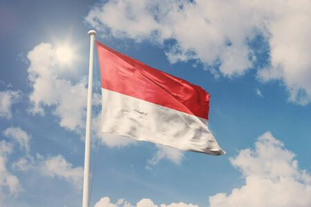 National symbol waving against cloudy, blue sky, sunny day
