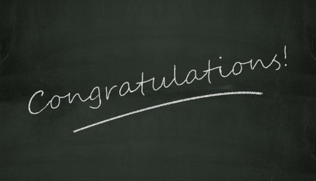 Illustration of congratulation written on black chalkboard Фото со стока