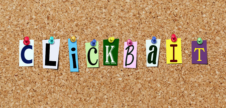 The word clickbait in cut out magazine letters pinned with thumbtak to cork noticeboard