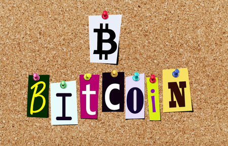 Illustration of bitcoin symbol and word blockchain in magazine cut out letters pinned on cork noticeboard