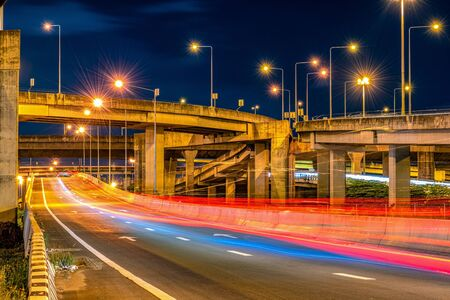 Underside of an elevated roads Expressway bridge and traffic at night 写真素材
