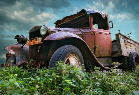 An old vintage rustic red colored truck on a field with cloudy sky background Stock Photo