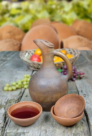 A traditional Georgian wine jug and set of clay cups on a old wooden table Archivio Fotografico