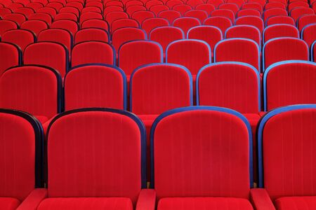Empty red chairs in concert hall