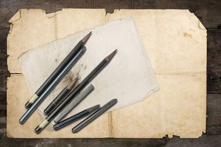 Drawing pencils and graphites on old papers, on awooden grunge table