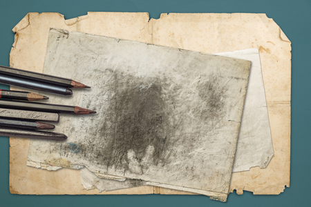 Drawing pencils and graphites on the old papers, with blue paper background