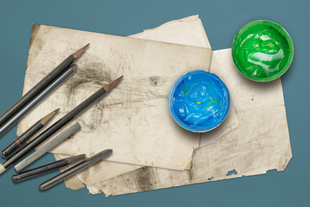 Drawing pencils, graphites and paints on the old papers, with blue paper background