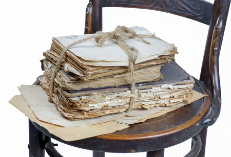 Old books and papers tied with a rope on a old wooden chair, white background isolated Banco de Imagens