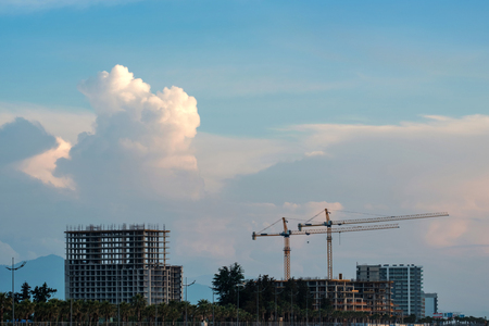 non finished constructions and cranes with blue cloudy sky background