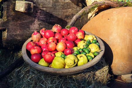 Apples quinces and kivi fruits in the wooden bowl