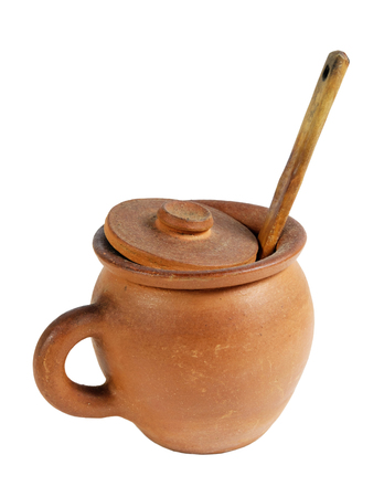 clay pot with wooden spoon on white background, isolated