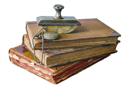 Pile of old books with pocket watch on a white background, isolated