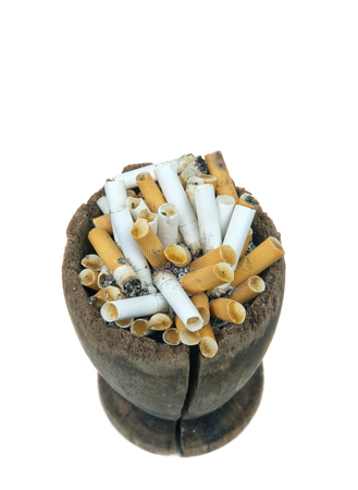 Cracked wooden ashtray with full of smoked cigarettes, white background
