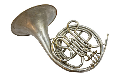 Old vintage silver French horn on a white background, isolated