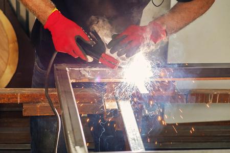 Worker welding metal construction in the workshop