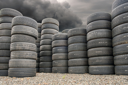 Pile of old tires on the ground, dramatic smoky sky background 版權商用圖片
