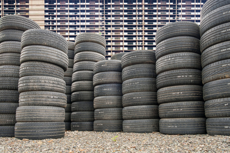 pile of old car tires on the ground, industrial background