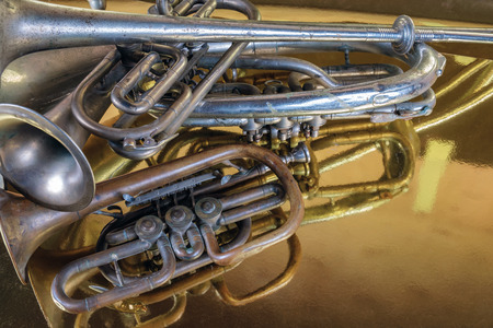 Brass instruments reflected on a golden surface 写真素材