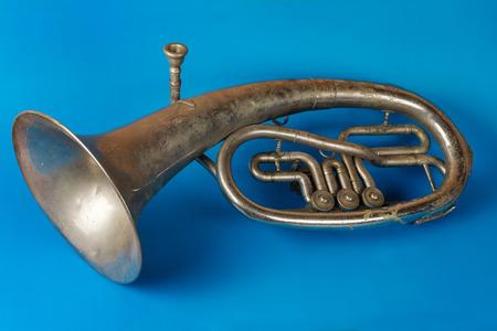Old vintage tenor horn on a blue background